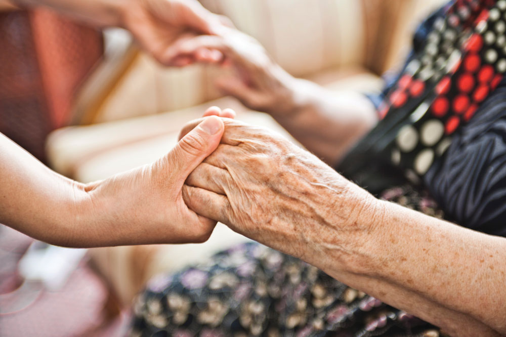 Charter Senior Living of Vernon Hills resident clasping hands with younger friend